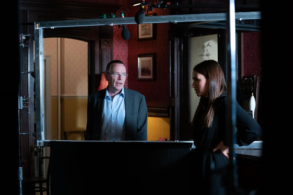 Adam Woodyatt and Milly Zero filming on the 'EastEnders' set separated by a Perspex screen. (BBC)