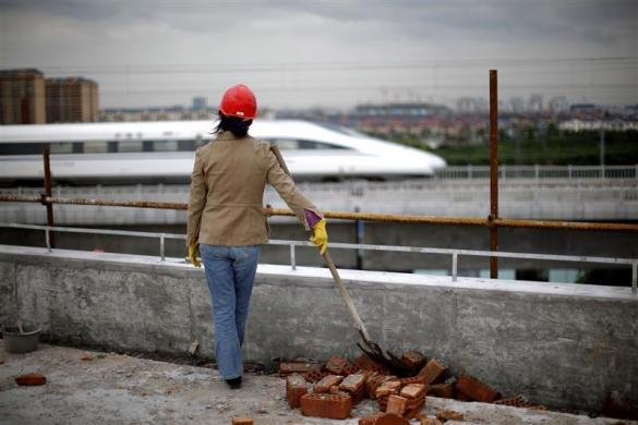 A female construction worker watches a train pass on the new high-speed railway line between Shanghai and Hangzhou on the outskirts of Shanghai, October 26, 2010.