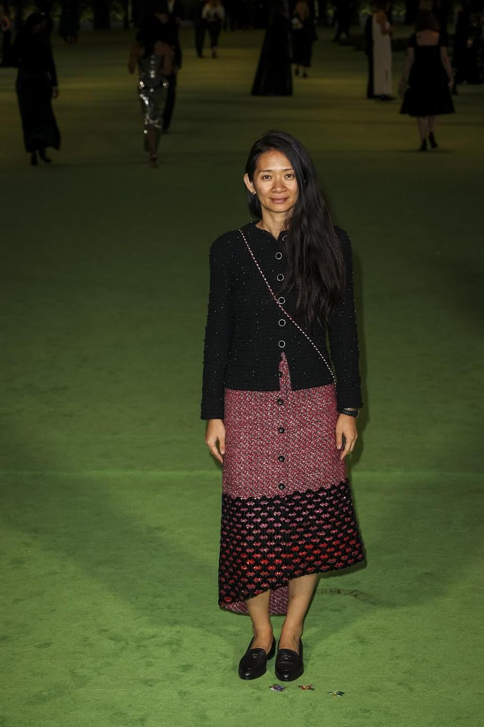 A woman in a black, button-down shirt and pink skirt posing on a green carpet