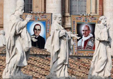 Pope Paul VI and El Salvador's Archbishop Oscar Romero pictures are seen during a Mass for their canonisation at the Vatican