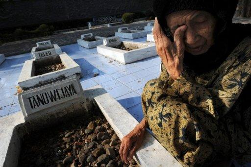 Indonesian widow Anti Rukiyah, is seen in 2011 visiting the tomb of her husband Saleh Tanuwijaya