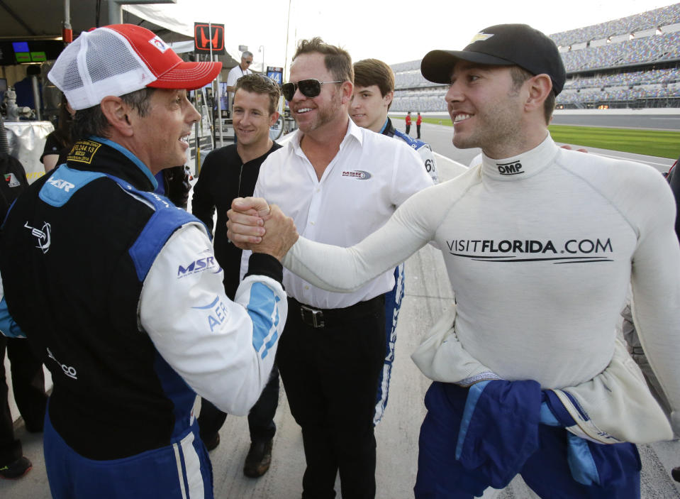 FILE - Oswaldo Negri, Jr., left, of Brazil, is congratulated by driver Michael Valiante, right, after winning the pole position for the IMSA 24-hour auto race as co-driver AJ Allmendinger, second from left, car owner Michael Shank, center, and co-driver Matt McMurry, second from right, celebrate on pit road at Daytona International Speedway in Daytona Beach, Fla., in this Thursday, Jan. 22, 2015, file photo. It took Michael Shank years to break into IndyCar even as the small-time team owner did everything the right way. The long winding road finally crossed the finish line for the biggest win in team history, an improbable Indianapolis 500 victory that gave Shank the validation he's sought for so long. (AP Photo/John Raoux, File)