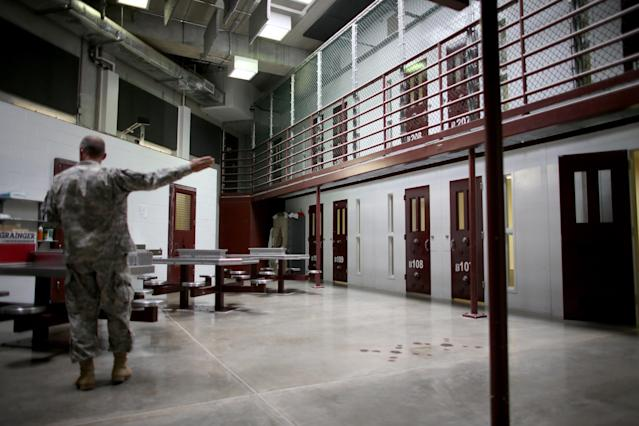 GUANTANAMO BAY, CUBA - JUNE 25: (EDITORS NOTE: Image has been reviewed by the U.S. Military prior to transmission.) A military officer stands near prison cells in camp 6 where prisoners are housed in a communal facility at the U.S. military prison for 'enemy combatants' on June 25, 2013 in Guantanamo Bay, Cuba. President Barack Obama has recently spoken again about closing the prison which has been used to hold prisoners from the invasion of Afghanistan and the war on terror since early 2002. (Photo by Joe Raedle/Getty Images)