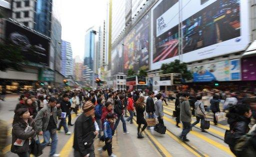 This file photo shows people crossing a street in Causeway Bay, one of Hong Kong's busiest retail districts. Causeway Bay has knocked New York's Fifth Avenue off the top of the list of most expensive places to rent retail space in the world, according to the latest research