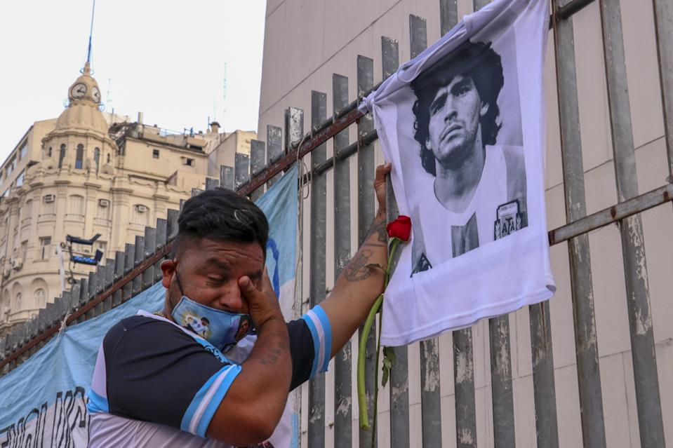 An Argentinian fan weeps in front of a portrait of Diego Maradona following news of his death. Three days of mourning was declared in his country. (PHOTO: Muhammed Emin Canik/Anadolu Agency via Getty Images)