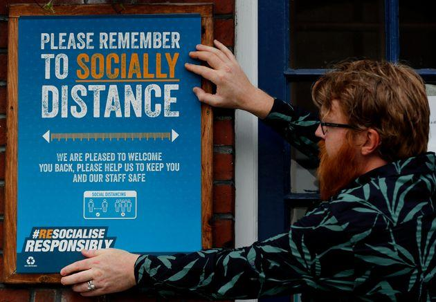 Are Kjetil Kolltveit puts up social distancing signs at the Chandos Arms pub in London ahead of 'Super Saturday'