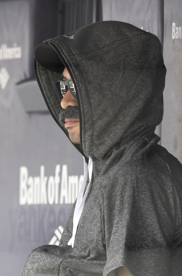 Ichiro Suzuki, special assistant to the chairman of the Seattle Mariners, wears a fake mustache and a hoodie as he sits in the dugout and watches the New York Yankees bat during the first inning of a baseball game Thursday, June 21, 2018, at Yankee Stadium in New York. Suzuki donned a Bobby Valentine-style disguise and sneaked into the Seattle dugout to watch a bit of the action. (AP Photo/Bill Kostroun)