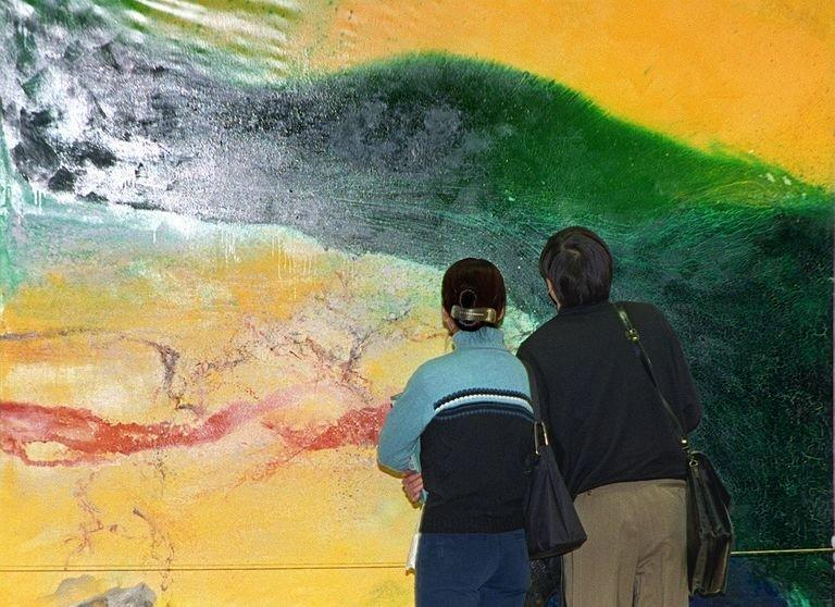 Visitors look at an abstract oil painting by Zao Wou-ki at an exhibition in Beijing, March 4, 1999. Zao, a significant figure in 20th-century Chinese art, died Tuesday at his home in Switzerland aged 93, Marc Bonnant, a lawyer for his wife, told AFP