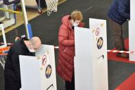 Kosovo Albanians cast their votes during Parliamentary elections at a polling station in Pristina