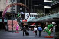 People walk by an area of the city following the implementation of stricter social-distancing and self-isolation rules to limit the spread of the coronavirus disease (COVID-19) in Sydney