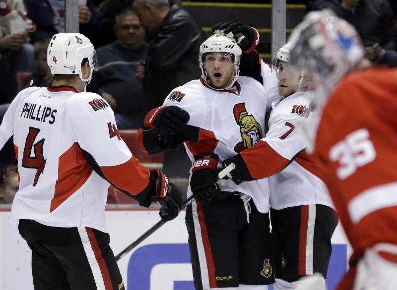 Ottawa Senators right wing Bobby Ryan, center, is congratulated on his goal by teammates Chris Phillips (4) and Kyle Turris (7) as Detroit Red Wings goalie Jimmy Howard, right, skates back to the net during the first period of an NHL hockey game in Detroit, Wednesday, Oct. 23, 2013. (AP Photo/Carlos Osorio)