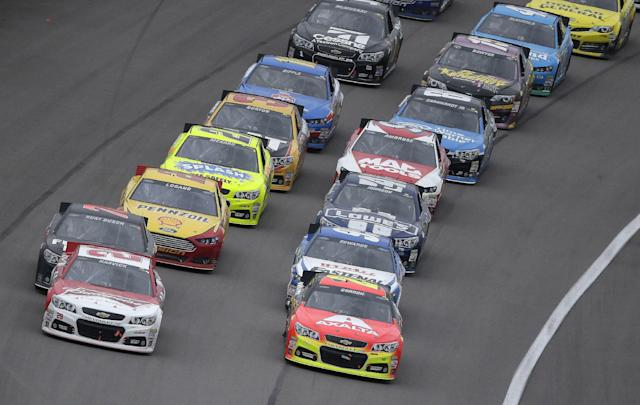 Driver Kevin Harvick, front left, leads the pack coming out of a caution with 20 laps to go in the NASCAR Sprint Cup series auto race at Kansas Speedway in Kansas City, Kan., Sunday, Oct. 6, 2013. Harvick went on to win the race. (AP Photo/Charlie Riedel)