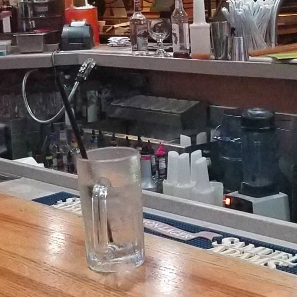 An opossum appeared tucked away behind the bar of the Applebee's restaurant in Columbia. Source: Facebook/ Adriane Neico