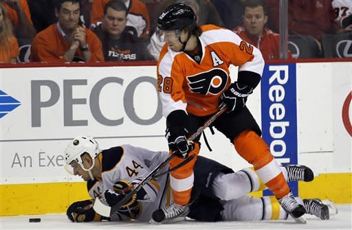 Buffalo Sabres defenseman Andrej Sekera (44), from Slovakia, keeps his eye on the puck after falling to the ice with Philadelphia Flyers center Claude Giroux (28) above him in the first period of an NHL hockey game on Thursday, April 5, 2012, in Philadelphia. (AP Photo/Alex Brandon)