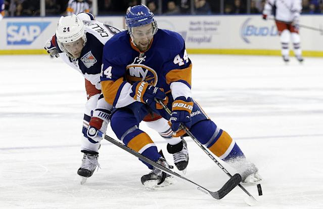 New York Rangers' Ryan Callahan (24) and New York Islanders' Calvin de Haan (44) fight for control of the puck during the second period of an NHL hockey game on Friday, Jan. 31, 2014, in New York. (AP Photo/Frank Franklin II)