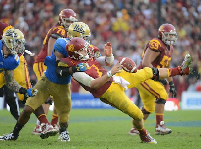 PASADENA, CA - NOVEMBER 17: Matt Barkley #7 of the USC Trojans is hit by Anthony Barr #11 of the UCLA Bruins as he throws during the third quarter at Rose Bowl on November 17, 2012 in Pasadena, California. (Photo by Harry How/Getty Images)