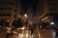 Teargas canisters fly during anti-government protest following Tuesday's massive explosion which devastated Beirut, Lebanon, Sunday, Aug. 9. 2020. (AP Photo/Hassan Ammar)