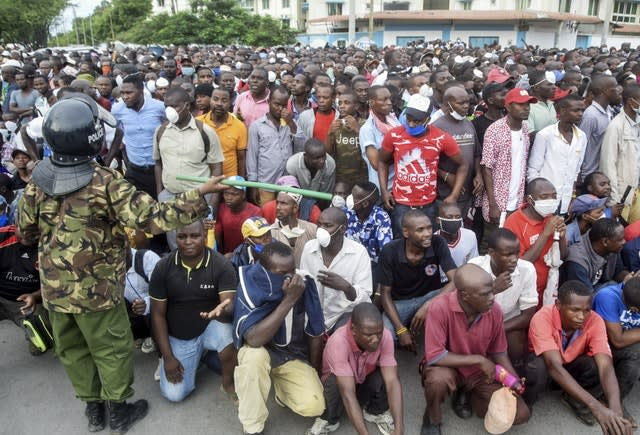 Kenyan police hold back ferry passengers in Mombasa