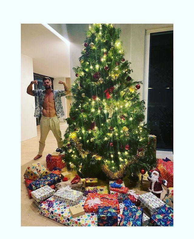 """<p>""""Santa brought me a Thor action figure for Christmas,"""" the actress joked of her beefy husband, who flexed next to a giant pile of gifts in their Australian home.</p>"""