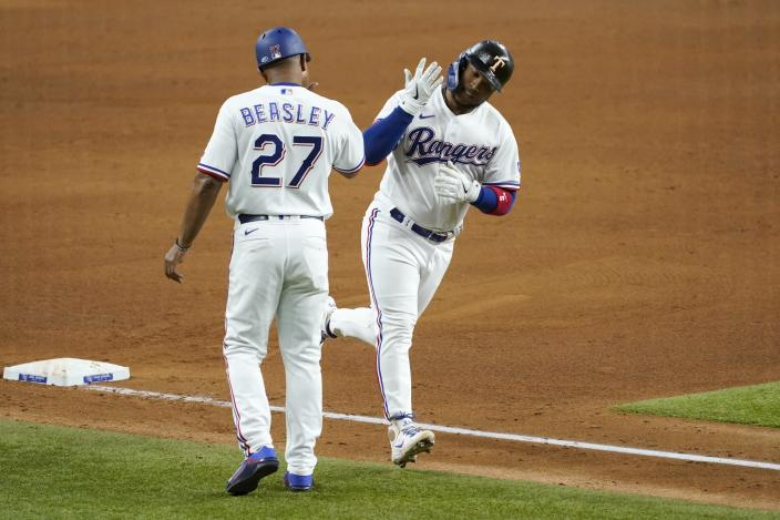 Texas Rangers third base coach Tony Beasley (27) celebrates with Willie Calhoun, right, as he runs home after hitting a solo home run off of New York Yankees starting pitcher Gerrit Cole in the fifth inning of a baseball game in Arlington, Texas, Monday, May 17, 2021. (AP Photo/Tony Gutierrez)