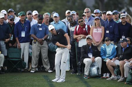 Rory McIlroy of Northern Ireland chips from amid the crowd to the 18th green during first round play of the 2018 Masters golf tournament at the Augusta National Golf Club in Augusta, Georgia, U.S., April 5, 2018. REUTERS/Mike Segar