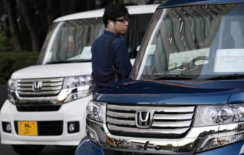 A man inspects Honda vehicles displayed in front of Honda Motor Co. headquarters in Tokyo Monday, Oct. 29, 2012. Honda's quarterly profit surged 36 percent as Japanese automakers bounced back from last year's tsunami disaster in northeastern Japan, but the company lowered its annual forecasts Monday because of a sales plunge in China. (AP Photo/Koji Sasahara)