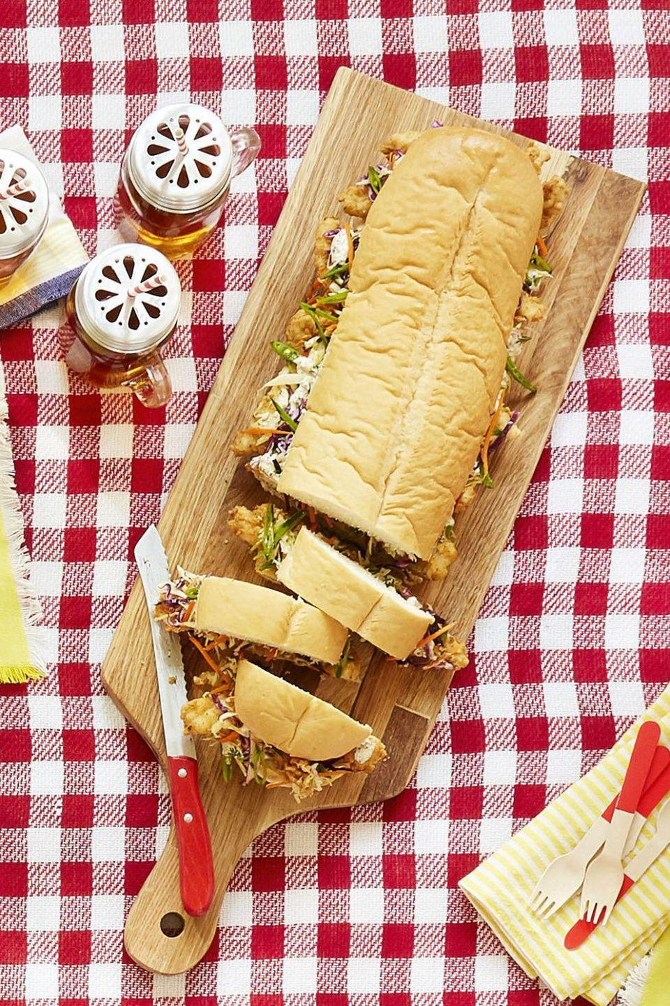"""<p>A big sub sandwich will feed plenty of people at your Memorial Day party.</p><p><strong><a href=""""https://www.countryliving.com/food-drinks/recipes/a42427/chicken-finger-sub-cabbage-slaw-recipe/"""" rel=""""nofollow noopener"""" target=""""_blank"""" data-ylk=""""slk:Get the recipe"""" class=""""link rapid-noclick-resp"""">Get the recipe</a>.</strong></p><p> <a class=""""link rapid-noclick-resp"""" href=""""https://www.amazon.com/JAMIE-OLIVER-Acacia-Cutting-Board/dp/B01D6KCNU0?tag=syn-yahoo-20&ascsubtag=%5Bartid%7C10050.g.3290%5Bsrc%7Cyahoo-us"""" rel=""""nofollow noopener"""" target=""""_blank"""" data-ylk=""""slk:SHOP CUTTING BOARDS"""">SHOP CUTTING BOARDS</a></p>"""