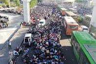 Migrant workers and their family members lineup outsdie the Anand Vihar bus terminal to leave for their villages during a government-imposed nationwide lockdown as a preventive measure against the COVID-19 coronavirus in New Delhi on March 28, 2020. - Tens of thousands of migrant workers and their famiies on March 28 fought and shoved their way onto buses organised by India's most populous state to get them to their home towns amid the coronavirus pandemic. (Photo by Bhuvan BAGGA / AFP) (Photo by BHUVAN BAGGA/AFP via Getty Images)