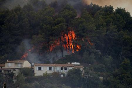 Flames from a burning wildfire are see near homes in Carros, near Nice, France, July 24, 2017.   REUTERS/Eric Gaillard