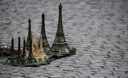 FILE PHOTO: Eiffel Tower souvenirs displayed by a street vendor are seen on the pavement next to the Sacre Coeur (Sacred Heart) basilica in Paris, France, July 31, 2017.  REUTERS/Christian Hartmann/File Photo