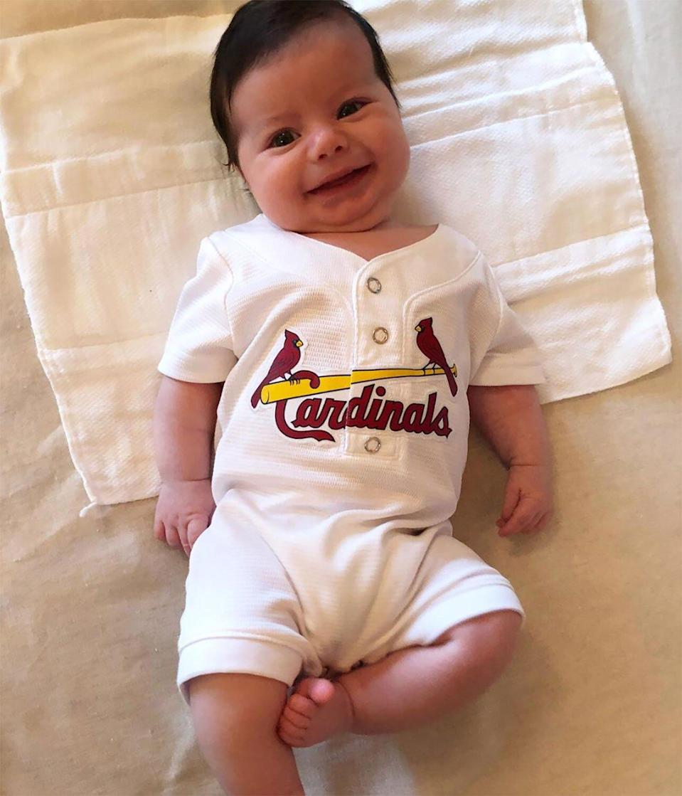 """He's already a Cardinals fan! Ben celebrated Opening Day with a onesie jersey gifted from Cardinals pitcher Michael Wacha. """"Smile if you're excited!"""" proud dad Andy <a href=""""https://www.instagram.com/p/Bv4V7D_lyBD/"""" rel=""""nofollow noopener"""" target=""""_blank"""" data-ylk=""""slk:captioned"""" class=""""link rapid-noclick-resp"""">captioned</a> the photo."""