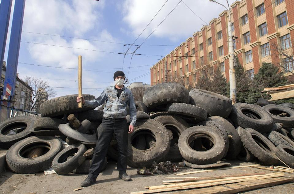 A masked pro-Russian activist poses for a photo in front of barricades at the Ukrainian regional office of the Security Service in Luhansk, 30 kilometers (20 miles) west of the Russian border, in Ukraine, Wednesday, April 9, 2014. Ukrainian Interior Minister Arsen Avakov said the standoff in Luhansk and the two neighboring Russian-leaning regions of Donetsk and Kharkiv must be resolved within two days.(AP Photo/Igor Golovniov)
