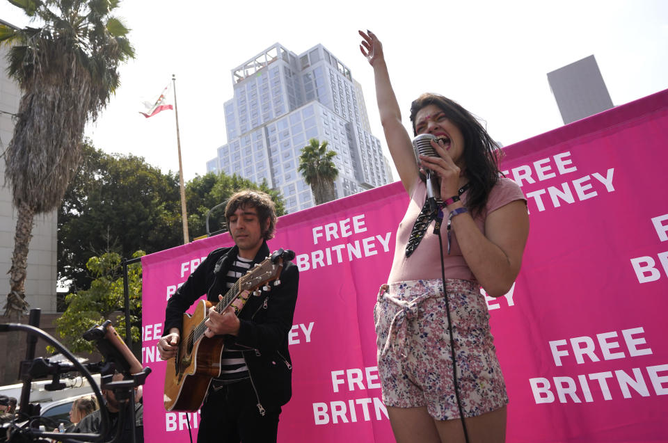 Britney Spears supporters Adrian Johnson, left, and Lucy Hall perform Spears' songs outside the Stanley Mosk Courthouse, Wednesday, Sept. 29, 2021, in Los Angeles. A Los Angeles judge will hear arguments at a hearing Wednesday over removing Spears' father from the conservatorship that controls her life and money and whether the legal arrangement should be ended altogether. (AP Photo/Chris Pizzello)