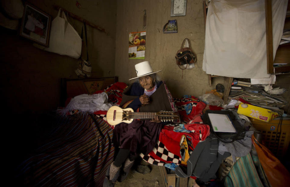 """Ms Flores Colque holds a """"charango"""", a small Andean stringed instrument, at her home in Sacaba, Bolivia (Picture: AP)"""