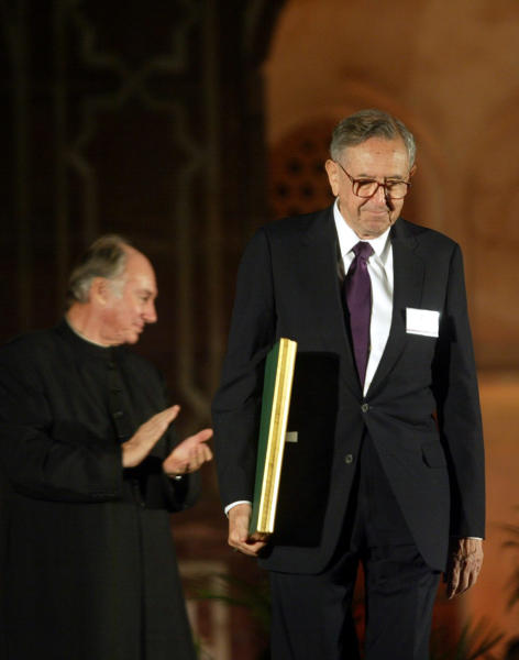 FILE - In this Nov. 27, 2004 file photo, Cesar Pelli of Cesar Pelli and Associates US, right, one of the awardees of the Aga Khan Award for Architecture walks with his award as the Aga Khan, spiritual leader of the Shia Imami Ismaili Muslims, claps during the award ceremony at the gardens of Emperor Humayuns Tomb in New Delhi, India. Pelli, known for designing some of the world's tallest and most iconic buildings, has died. He was 92.  Anibal Bellomio, a senior associate architect at Pelli's Connecticut studio, confirmed Saturday, July 20, 2019,  that Pelli died peacefully on Friday at his home in New Haven.  (AP Photo/Manish Swarup)