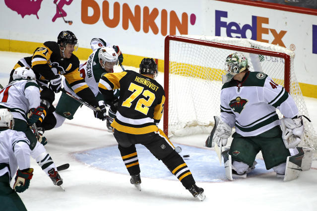 Pittsburgh Penguins' Evgeni Malkin (71) puts the puck behind Minnesota Wild goaltender Devan Dubnyk (40), with Jared Spurgeon (46) defending, for a goal during the first period of an NHL hockey game in Pittsburgh, Tuesday, Jan. 14, 2020. (AP Photo/Gene J. Puskar)