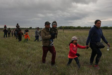 Migrant families seeking asylum walk through field after illegally crossing into the U.S. from Mexico in Penitas, Texas