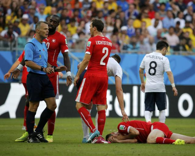 Switzerland's Steve von Bergen lies injured on the ground as Switzerland's Stephan Lichtsteiner (2) talks to referee Bjorn Kuipers of the Netherlands during their 2014 World Cup Group E soccer match against France at the Fonte Nova arena in Salvador June 20, 2014. REUTERS/Jorge Silva (BRAZIL - Tags: SOCCER SPORT WORLD CUP)