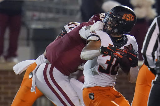 Oklahoma defensive end Ronnie Perkins, left, grabs the face mask of Oklahoma State running back Chuba Hubbard (30) during a tackle in the second half of an NCAA college football game in Norman, Okla., Saturday, Nov. 21, 2020. (AP Photo/Sue Ogrocki)