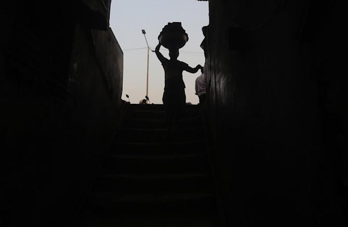A worker carries a load of bricks