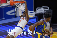 New York Knicks guard RJ Barrett (9) hangs from the rim after dunking next to Golden State Warriors center James Wiseman during the second half of an NBA basketball game in San Francisco, Thursday, Jan. 21, 2021. (AP Photo/Jeff Chiu)