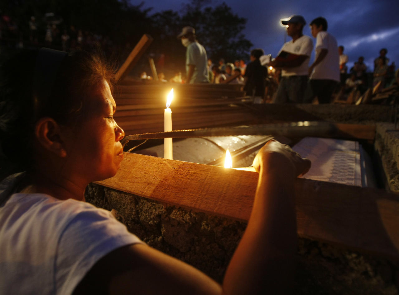 A relative lights candles at the coffins of victims of Friday's flash flooding Tuesday Dec. 20, 2011 at a public cemetery in Iligan city in southern Philippines. Dozens of grieving relatives of the victims wept openly during funeral rites presided by a Catholic bishop at nightfall in Iligan city. (AP Photo/Bullit Marquez)
