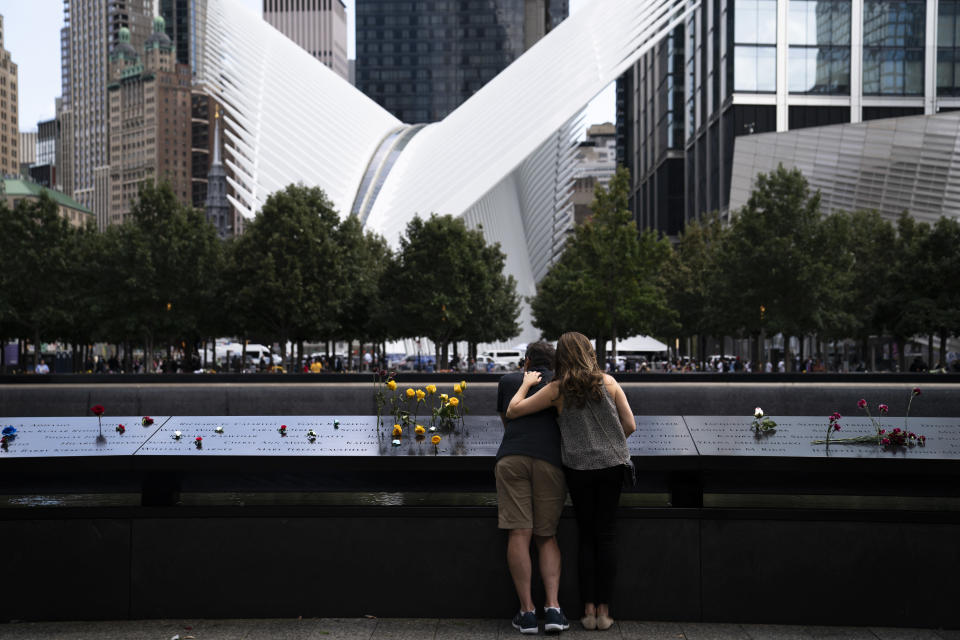 Mourners stand at the rim of the north pool with the white World Trade Center Oculus in the background after the conclusion of ceremonies to commemorate the 20th anniversary of the Sept. 11 terrorist attacks, Saturday, Sept. 11, 2021, at the National September 11 Memorial & Museum in New York. (AP Photo/John Minchillo)