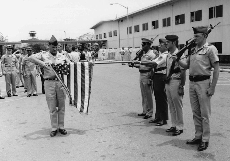 FILE - In this March 29, 1973 file photo, the American flag is furled at a ceremony marking official deactivation of the Military Assistance Command-Vietnam (MACV) in Saigon, after more than 11 years in South Vietnam. While the fall of Saigon in 1975 — with its indelible images of frantic helicopter evacuations — is remembered as the final day of the Vietnam War, March 29 marks an anniversary that holds greater meaning for many who fought, protested or otherwise lived the war. (AP Photo/Charles Harrity, File)