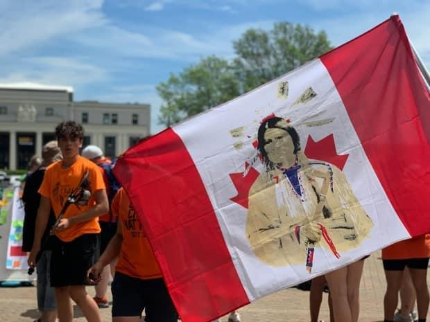 An attendee of a memorial at Halifax's Peace and Friendship Park holds up a Canadian flag with an Indigenous man painted over the maple leaf. (Taryn Grant/CBC - image credit)