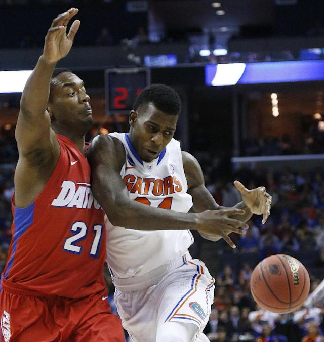 Florida forward Casey Prather (24) collides with Dayton forward Dyshawn Pierre (21) during the first half in a regional final game at the NCAA college basketball tournament, Saturday, March 29, 2014, in Memphis, Tenn. (AP Photo/Mark Humphrey)