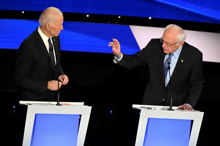 Democratic presidential hopefuls former Vice President Joe Biden (L) and Senator Bernie Sanders -- seen at a debate in Iowa in January 2020 -- are running close to each other in the polls as the Iowa caucuses approach