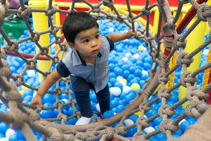 little boy playing inside a tunnel in the playground balls poll