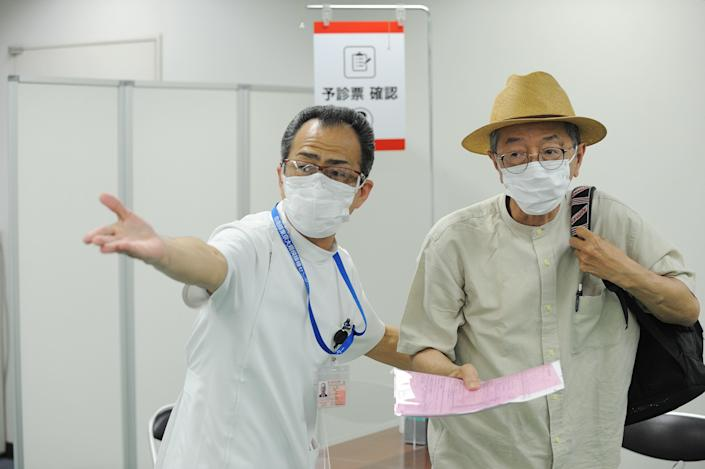 A medical worker guides a person at a coronavirus mass vaccination center, June 9, 2021 in Tokyo, Japan. / Credit: DAVID MAREUIL/Getty