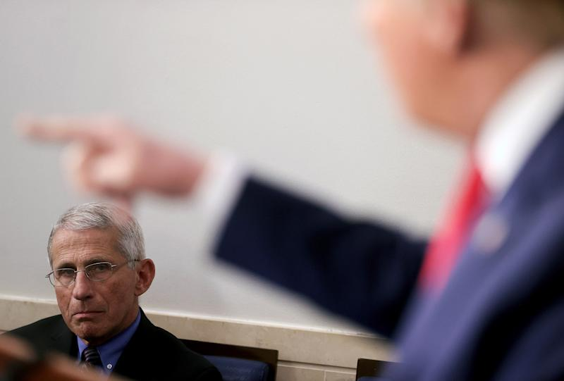Dr. Anthony Fauci, director of the National Institute of Allergy and Infectious Diseases, listens as U.S. President Donald Trump addresses the daily coronavirus task force briefing at the White House on April 9, 2020. (Jonathan Ernst/Reuters)
